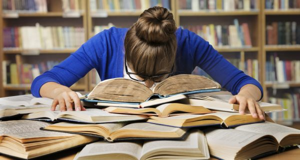Girl studies for post-graduate degree with head in her books